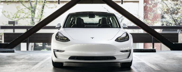 White Tesla Parked in a Parking Garage