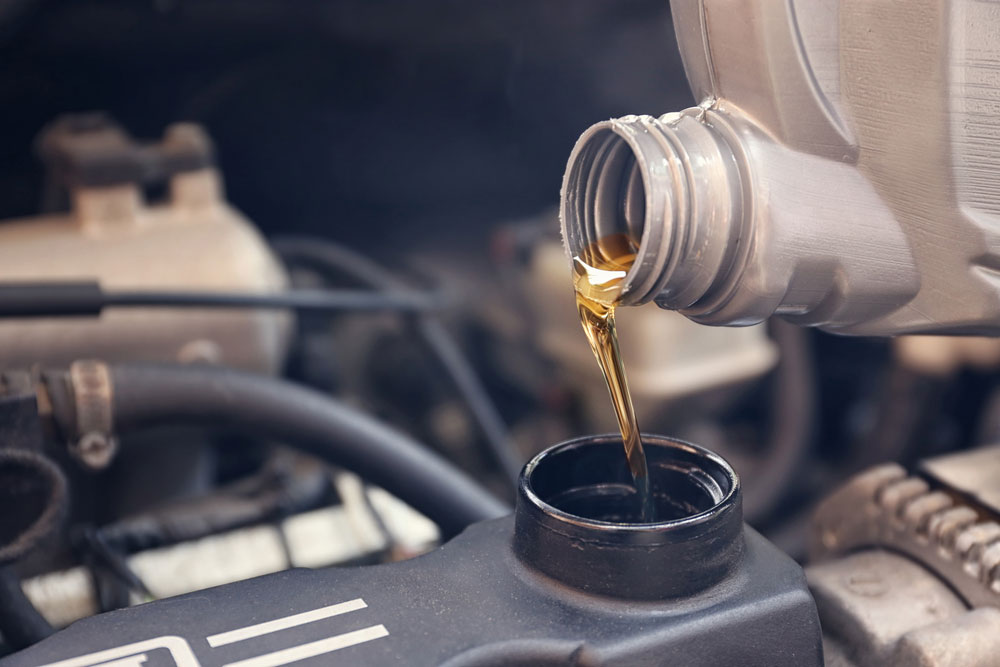Mechanic pouring synthetic oil into an engine