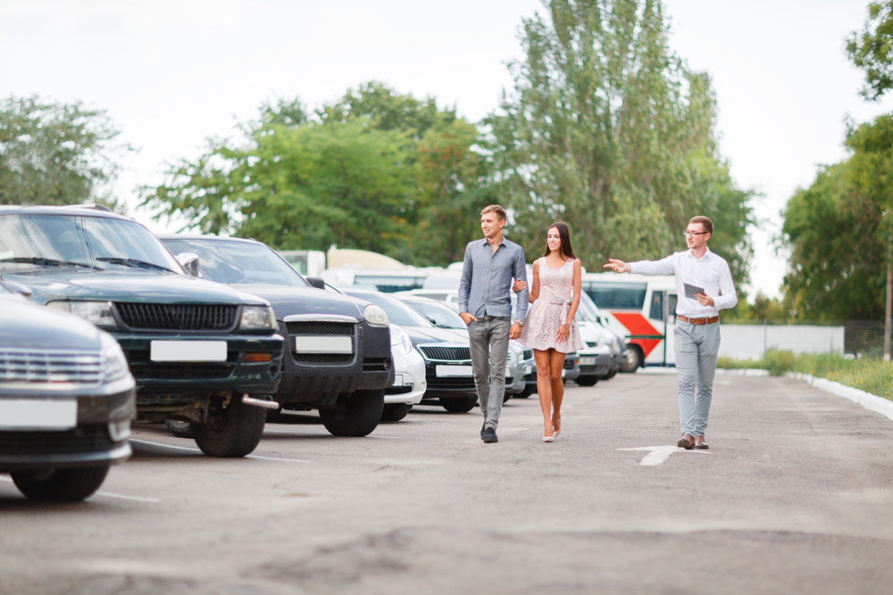 Young Couple At A Used Car Dealership