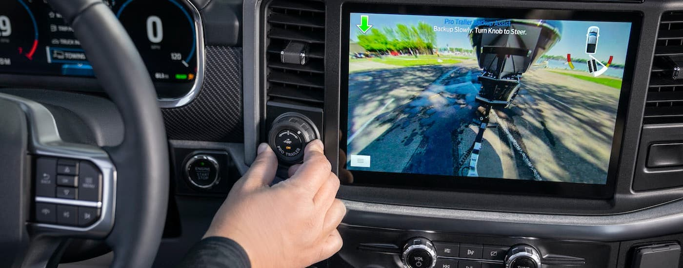 A close up shows someone turning a knob using Pro Trailer Assist in a 2021 Ford F-150.