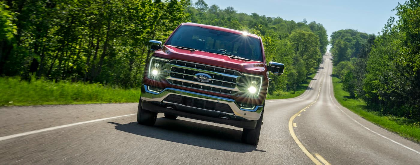 A red 2021 Ford F-150 is shown driving down an empty road.