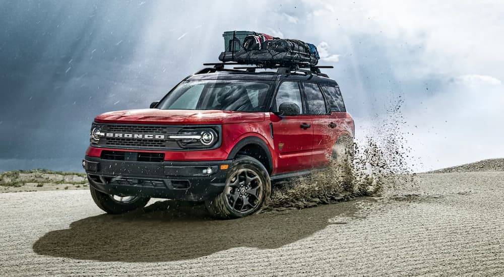 A red 2021 Ford Bronco Sport is shown off-roading through a desert after leaving a Citrus Heights Ford dealership.