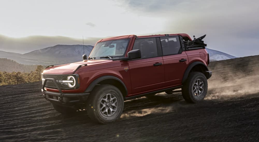 A red 2021 Ford Bronco is shown from the side driving in the mountains.