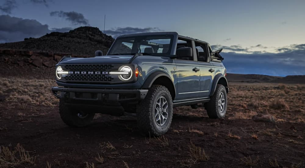 A blue 2021 Ford Bronco is shown from the front parked in a desert at night.