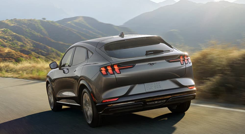A grey 2021 Ford Mustang Mach-E is shown from the rear driving on a road in the mountains after leaving a Folsom Ford dealership.