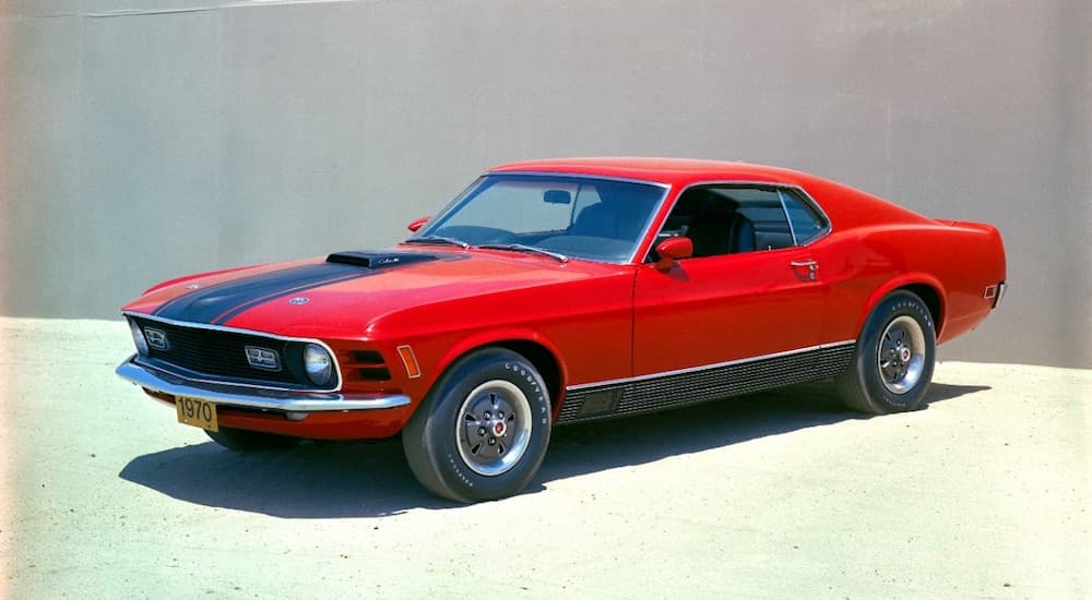 A red 1970 Ford Mustang Mach 1 is shown parked inside of a Roseville Ford dealer.