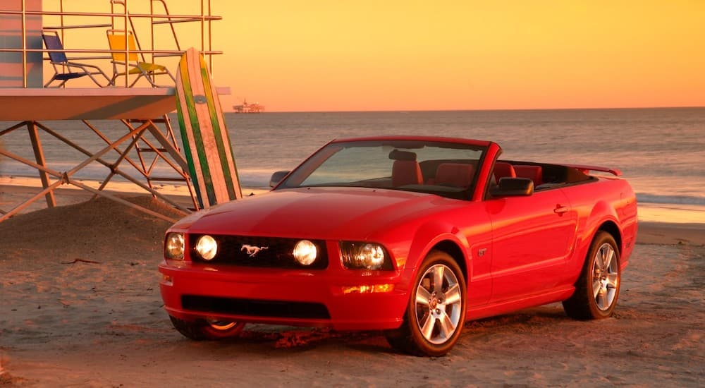 A red 2005 Ford Mustang GT is shown parked on a beach at sunset.