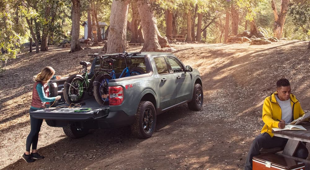 A green 2022 Ford Maverick is shown in the woods with bikes in the bed.