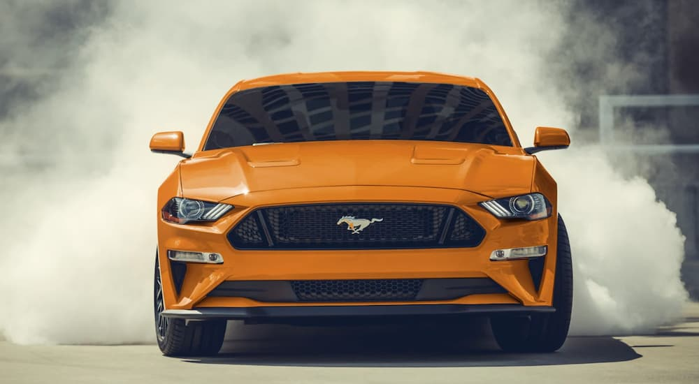 An orange 2021 Ford Mustang is shown from the front after leaving a Woodland Ford dealer.