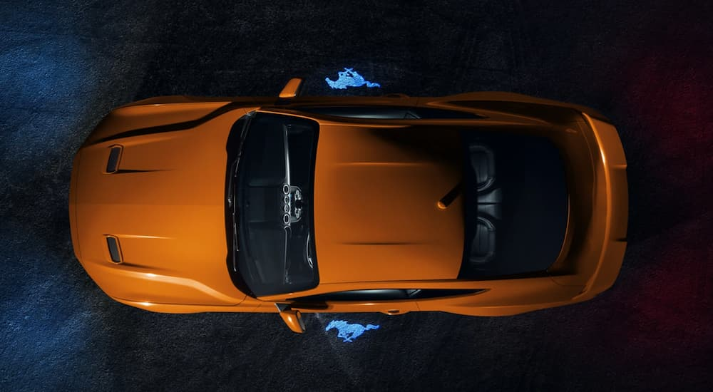 An orange 2021 Ford Mustang is shown from above at night.