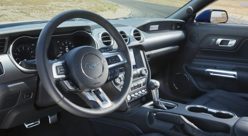 The black interior of a 2021 Ford Mustang shows the steering wheel and infotainment screen.