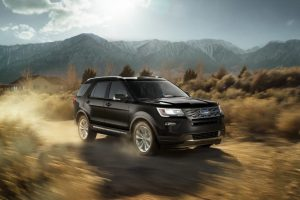 Image of black Ford Explorer driving in a desert.
