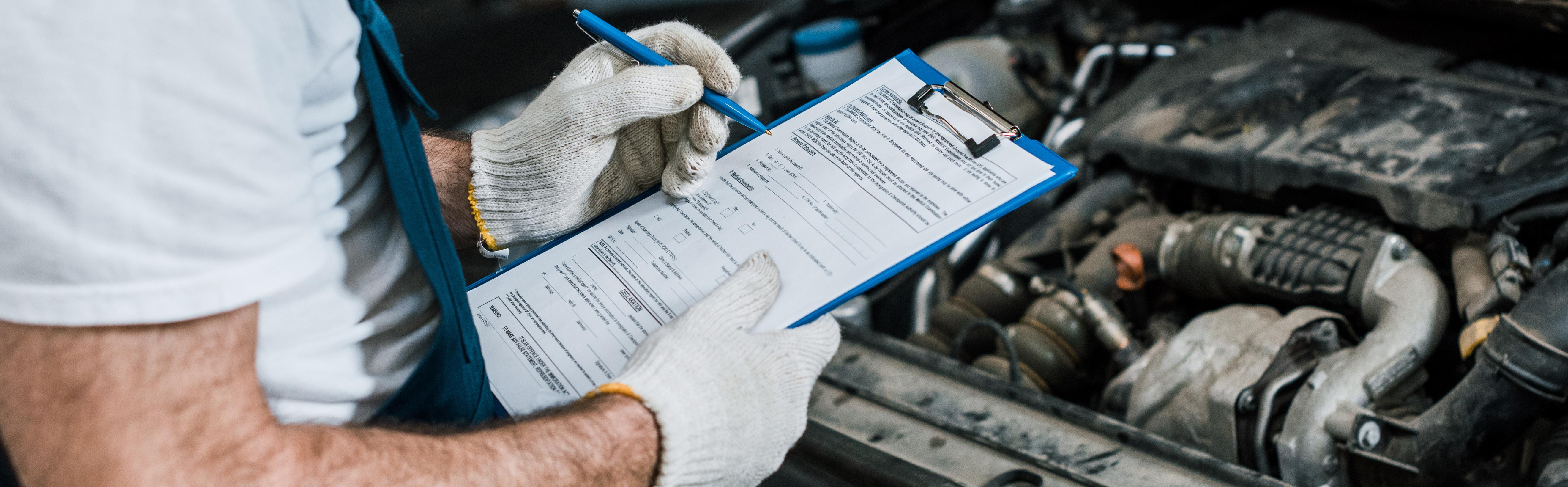 Panoramic Shot Of Repairman Holding Pen And Clipboard Near Car