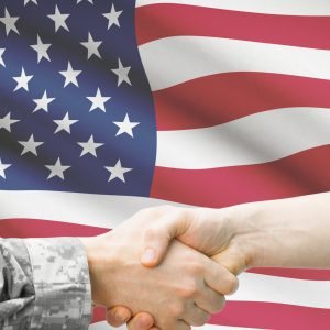 Soldier And Doctor Shaking Hands With Flag On Background Unite