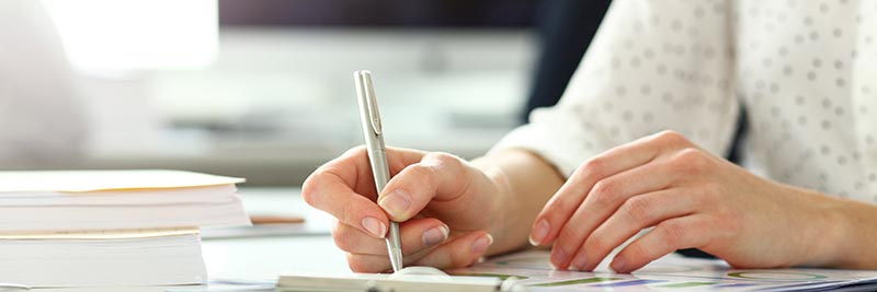 Female Hand Holding Silver Pen Working With Financial Document