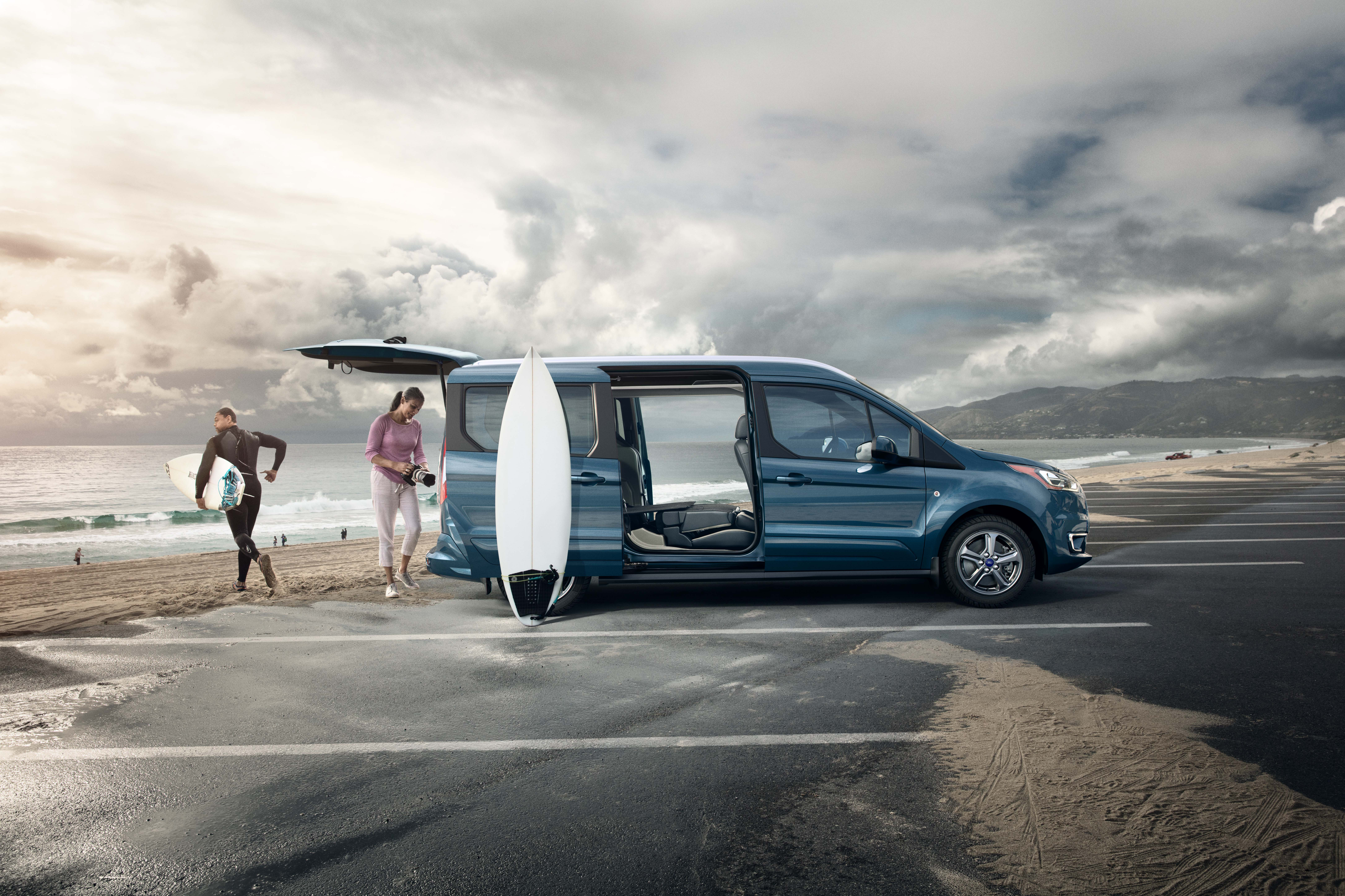 Couple surfing next to parked 2019 Ford Transit Connect